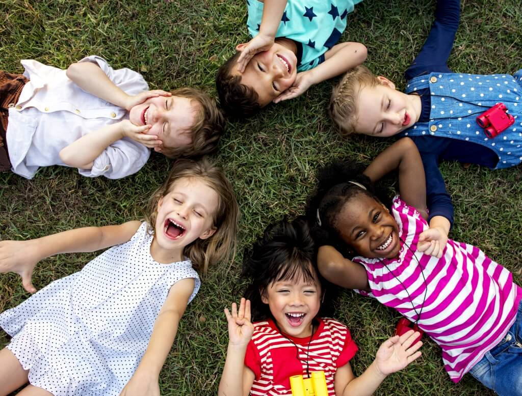young kids lying smiling on park grass