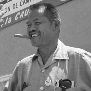 Larry Itliong smoking cigar smiling black and white image